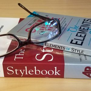 Image of reading glasses sitting on top of the Elements of Style and the AP Stylebook
